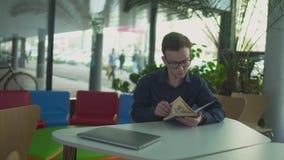 De student leest het boek in de bibliotheek stock videobeelden
