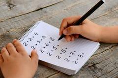 De student lost vermenigvuldigingsvoorbeelden op Het kind houdt een zwarte teller in zijn hand en schrijft antwoorden Stock Afbeelding