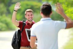 De student ontmoet zijn vriend en het golven van zijn hand Stock Foto's