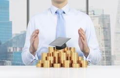 De student plaatst zijn handen over de graduatiehoed en de muntstukkenpiramide Een concept een hoge prijs voor het universitaire  royalty-vrije stock fotografie