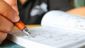 De student probeert om sudoku met kleurenpotlood als hobby a op te lossen royalty-vrije illustratie