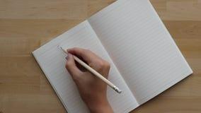De student schrijft Chinees karakter in notitieboekje met potlood stock videobeelden
