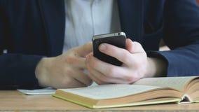 De student schrijft de tekst gebruikend een smartphone stock videobeelden