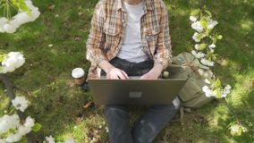 De student treft voor examens op het gazon in de schaduw van bloeiende de lentebomen voorbereidingen stock video