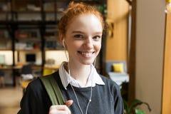 De student van de roodharigedame het stellen binnen in bibliotheek istening muziek met oortelefoons royalty-vrije stock foto