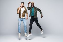 De student van twee het gemengde rasvrienden springen geïsoleerd op witte achtergrond Multiraciale vriendschap royalty-vrije stock foto's
