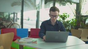 De student werkt met laptop in de bibliotheek stock footage