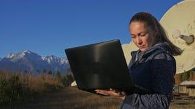 De studenteexploitant van instituut van Zonne Aardse Fysica controleert communicatieapparatuur in notitieboekje uniek stock video