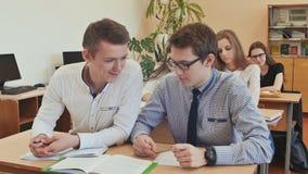 De studenten bestuderen in het klaslokaal bij de schoolbank stock video