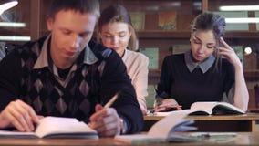 De studenten in bibliotheek concentreerden zich op hun boeken stock videobeelden