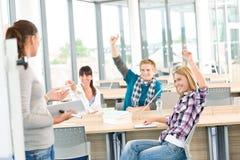 De studenten die van de middelbare school handen opheffen stock foto's