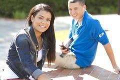 De studenten die van het meisje en van de jongen in openlucht ontspannen Stock Foto