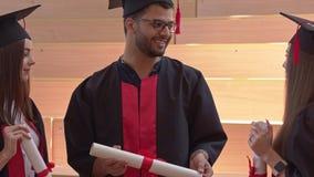 De studenten die van universiteit een diploma behalen spreken stock videobeelden
