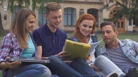 De studenten hebben pret op het gazon op campus royalty-vrije stock afbeelding