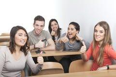 De studenten houden duimen tegen Stock Afbeelding