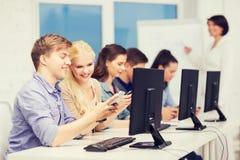 De studenten met computer controleren en smartphones stock foto