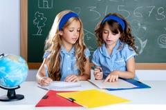 De studenten van jonge geitjes in klaslokaal dat elkaar helpt Royalty-vrije Stock Foto