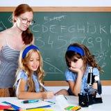 De studenten van jonge geitjes met de vrouw van de nerdleraar op school Royalty-vrije Stock Foto