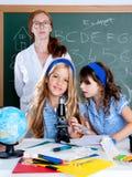 De studenten van jonge geitjes met de vrouw van de nerdleraar op school Stock Fotografie