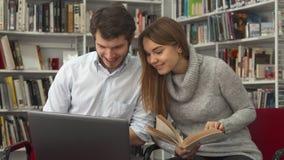 De studenten vergelijken informatie in het boek en over laptop bij de bibliotheek stock foto