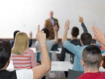 De studentengroep heft omhoog handen op klasse op royalty-vrije stock afbeelding