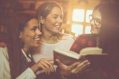 De studentenmeisjes in bibliotheeklezing boeken en hebbend conversa royalty-vrije stock fotografie