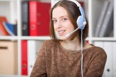 De studentenvrouw gebruikt een hoofdtelefoon met een microfoon voor online het leren universiteit Stock Foto's