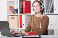 De studentenvrouw gebruikt een hoofdtelefoon met een microfoon voor online het leren universiteit Royalty-vrije Stock Foto