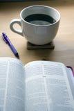 De studie van de psalmenbijbel met pen en koffie stock afbeelding