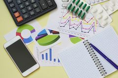 De studie van de doeltreffendheid van drugs Calculator, smartphone, Blocnote en tabletten op de lijst stock afbeelding