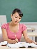 De studies van de student bij bureau in klaslokaal Stock Foto