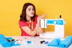 De studio die van de zitting van de meisjesnaaister bij wit bureau met naaimachine, spreding handen wordt geschoten, weet niet he royalty-vrije stock afbeelding