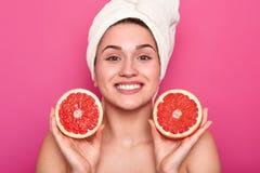 De studio van aantrekkelijke vrouw met grapefruit in haar handen en met witte handdoek op haar hoofd, wijfje na het nemen wordt g royalty-vrije stock foto's