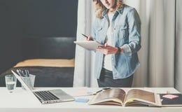 De studio van het bureauontwerp, jonge onderneemster in denimoverhemd die zich dichtbij Desktop bevinden en catalogus doorbladere stock fotografie