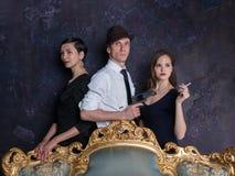 De studioschot van het detectiveverhaal Man en twee vrouwen Agent 007 Een man in een hoed met een pistool en twee vrouwen in zwar Stock Afbeeldingen
