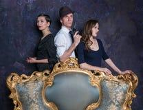 De studioschot van het detectiveverhaal Man en twee vrouwen Agent 007 Een man in een hoed met een pistool en twee vrouwen in zwar Royalty-vrije Stock Fotografie