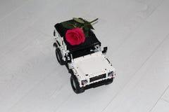 De stuk speelgoed auto SUV draagt echte rood toenam stock fotografie