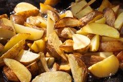 De stukken aardappels zijn gebraden in kokende olie Het koken procédé Het straatvoedsel stock afbeeldingen