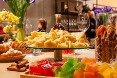De stukken Italiaanse parmezaanse kaas van de close-upplaat, bloemen, bakkerij, marmelade, bloemen, kaneel bij zich het richten o stock fotografie
