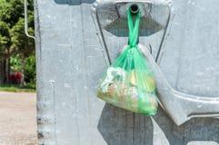 De stukken van brood in het plastiek of het nylon doen links op het metaalhuisvuil dumpster in zakken kunnen op de straat in de s stock afbeeldingen