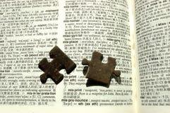 De stukken van de figuurzaag op een woordenboek Stock Foto's