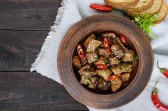 De stukken van gebraden varkensvlees met Spaanse pepers in een klei werpen op een donkere houten achtergrond Royalty-vrije Stock Fotografie