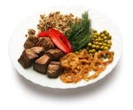 De stukken van gebraden vlees met versieren op een plaat Stock Foto's