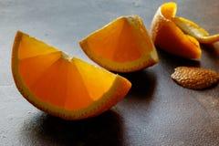 De stukken van sinaasappel op zwarte lijst sluiten omhoog Stock Foto