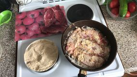 De stukken van vlees zijn gebraden in een hete pan Er zijn plonsen van heet vet De kok veegt op dit ogenblik de plak met een spon stock video