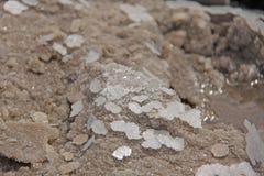 De stukken van zout liggen op het zand Macro Meer Baskunchak, Rusland stock foto