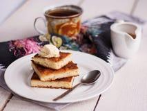 De stukkenkaastaart en een room, een lepel, gieten honing, koffie, Stock Afbeelding
