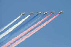 De su-25 aanvalsvliegtuigen met rook van bloemen van een vlag van Rusland stock afbeeldingen