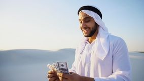 De succesvolle Arabische sjeik overweegt bankbiljetten en gelukkige, bevindende I royalty-vrije stock foto