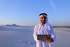De succesvolle Arabische zakenman houdt in handen en gebruikt tablet, s Stock Fotografie